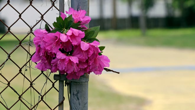 Flowers are placed on a fence near the site where Walter Scott was killed in North Charleston, S.C., Wednesday, April 8, 2015. Scott was killed by a North Charleston police officer after a traffic stop on Saturday.  The officer, Michael Thomas Slager, has been charged with murder. (AP Photo/Chuck Burton)