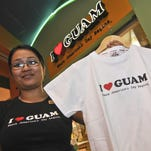 """Arlene Macapagal, I Love Guam store manager, displays a T-shirt printed with their company logo and the phrase,""""Where America's Day Begins,"""" at the retail store at Guam Premiere Outlets in January 2011."""