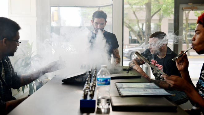 From left, The Eternal Vaper employees Chris Hill and Kyle Shreffler spend time in the shop with Adam Johnson of York and D'Angelo Manns of York on Saturday in York. The U.S. Food and Drug Administration announced new federal regulations that would make electronic cigarettes be regulated in much the same way as traditional cigarettes are. The regulations include banning people under the age of 18 from purchasing e-cigarette products, requiring companies to register and use only FDA-approved components in their products and banning free samples used to let potential customers taste flavors before purchasing. Stores and companies have about three months to comply with the new regulations.