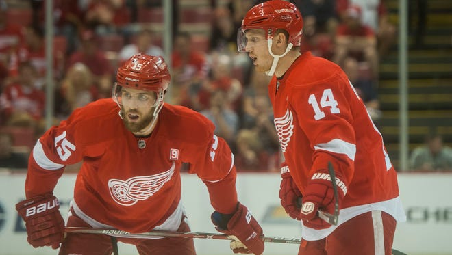 Red Wings forwards Riley Sheahan (15) and Gustav Nyqvist (14) have words before a face-off during the Wings' 5-1 win over the Senators Monday at Joe Louis Arena.