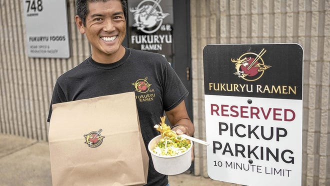 Fukuryu Ramen owner Jeff Tsao holds a rice bowl and a to-go bag Aug. 18 at his newly opened production kitchen, 748 Harmon Ave. in south Columbus.