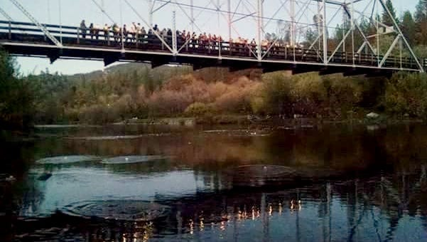 Family, friends and other well-wishers carry candles and drop flower petals off Old Lewiston Bridge on Saturday evening in honor of Stacey Smart, who's been missing for a year.