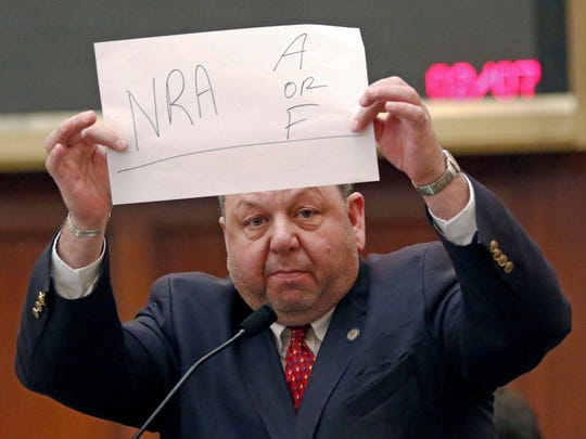"""Rep. Steve Holland, D-Plantersville, holds a hand-printed sign that says """"NRA A or F"""" as he argues Wednesday at the Capitol against proposed gun-rights legislation. House Bill 1083 is a measure that creates a process to challenge bans of carrying guns almost anywhere on government property, if the gun owner had a certain type of gun license. Holland argued that some lawmakers were supportive of the proposed law so as to receive an A grade from the National Rifle Association."""