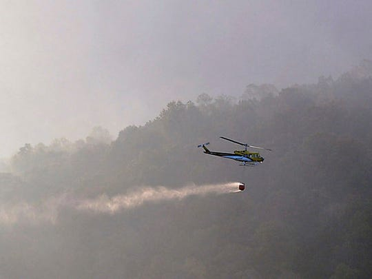 In this Wednesday, Nov. 9, 2016 photo, firefighters work at a wildfire burning near Lake Lure, N.C. A state of emergency is in effect for 25 western North Carolina counties where active wildfires are burning, caused by the drought that began last spring. Gov. Pat McCrory said in a news release Thursday that he was declaring the state of emergency for one-quarter of North Carolina's 100 counties. (Patrick Sullivan/The Times-News via AP)