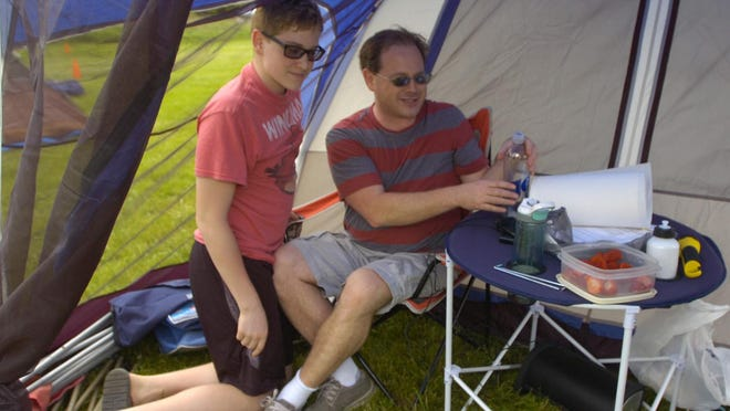 Taylor Bussey,13, and his dad, Scott, set up camp before the rain came.