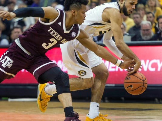 Texas A&M's Admon Gilder, left, knocks the ball away from Missouri's Kassius Robertson, right, during the second half of an NCAA college basketball game Tuesday, Feb. 13, 2018, in Columbia, Mo. Missouri won the game 62-58. (AP Photo/L.G. Patterson)