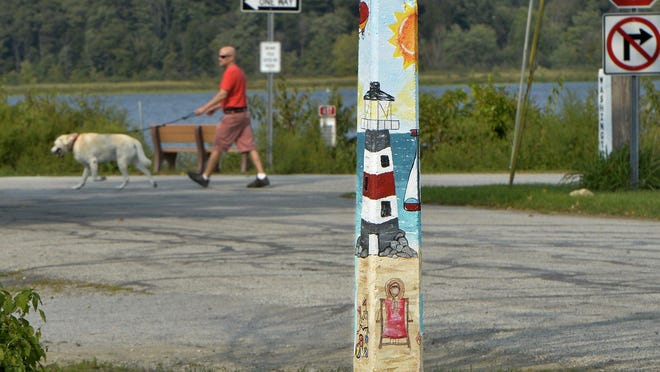 A painted signpost featuring a lighthouse and beach scene is located in the Lakeside neighborhood in Edinboro.