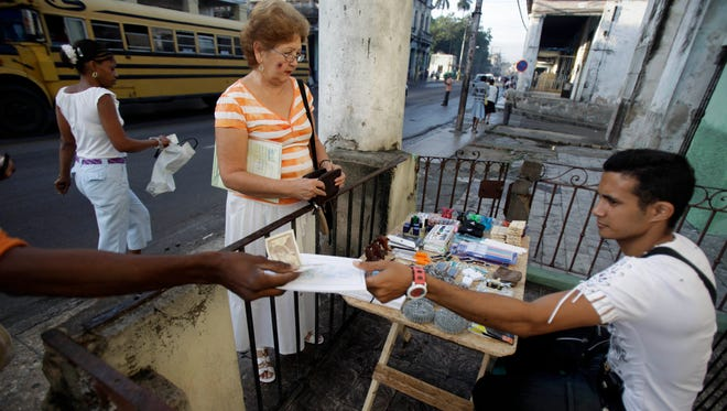 Eddy Cantallos attends to customers after receiving his new license to sell goods in front of a home in the El Cerro neighborhood in Havana. Cuba now has about 500,000 private entrepreneurs, many of whom are trying to work directly with U.S. businesses.