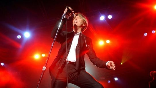 Bathed in light, David Bowie performs during a concert