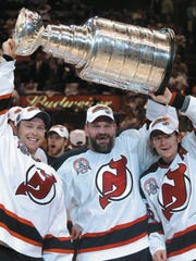 Martin Brodeur, Ken Danyeko and Patrik Elias hoist the cup after the Devils won in Game 7 of the Stanley Cup Finals, June 9, 2003.
