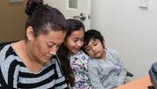 Guadalupe Carrera, 36, with her daughter Eva Maqueda, 9, and son Jose Maqueda, 5, fills out an application for health insurance assistance at El Proyecto Del Barrio Family Health Care Clinic on Jan. 8, 2015.