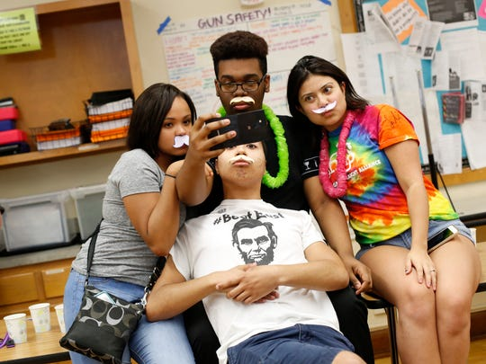 """Students Symphanee Fisher (clockwise from left), Quinzell McNeil, Carolina Ramos and David Ewing take mustached selfies Friday, May 20, 2016, as they participate in the """"It's a Boy"""" party in Jack Shuler's honor at Lincoln High School in Des Moines."""
