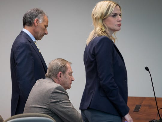 Judge Guy Williams sits between defense attorneys Lisa