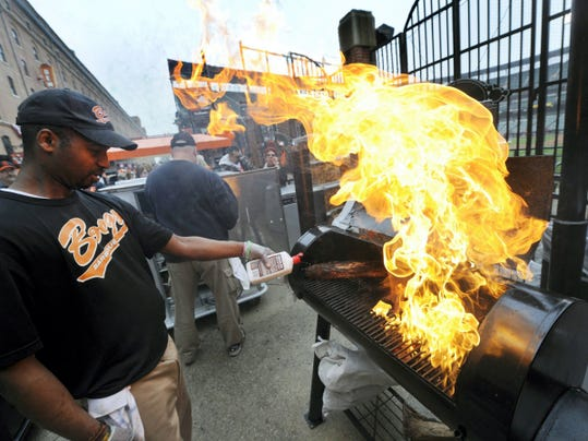 Arion Owens, an employee with Boog's BBQ, fires up a grill before the Baltimore Orioles' home opener. Some fans we spoke with said Boog's food is better than restaurants outside the stadium.