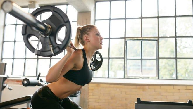 Female in sportswear doing squats in gym.