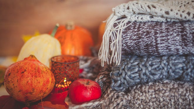 Still life autumn decoration made with pumpkins, apples, pomegranate, woolen scarves and candle