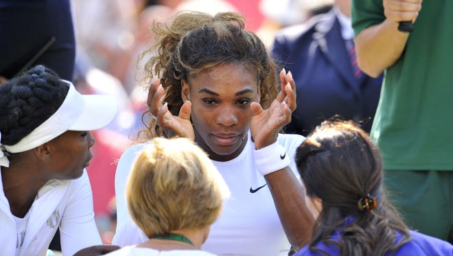 Serena Williams sits next to her partner sister  Venus as Serena was taken ill during their women's doubles second round match against Germany's Kristina Barrois and Switzerland's Stefanie Voegele.