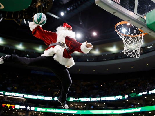a performer in a santa claus costume makes a trick dunk during a timeout in the fourth quarter of an nba basketball game between the boston celtics and the - Christmas Games Nba