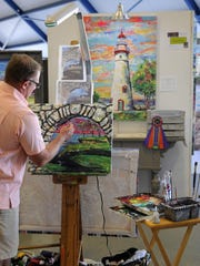Shaun Kinley, of Rocky River, paints the seventh piece in his Lake Erie series at the annual Appetite for the Arts at Liberty Aviation Museum on Saturday. Kinley took best of show during the eighth annual event.