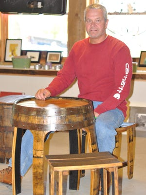 Tim Bertsch sits at one of the bistro sets he created out of reclaimed bourbon barrels. The woodworker says he enjoys working with wood that has strong ties to the state's rich heritage.