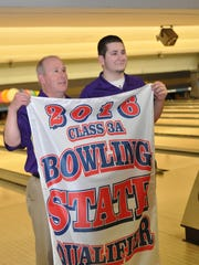 Johnston assistant coach Terry Hicks holds the Dragons' state qualifier banner with son Drew Hick. Drew finished second individually at the state meet with a 485 series.