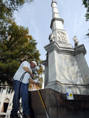 Vince Cunningham, with Augusta-Richmond County Facilities Management, uses a powerwasher on the Confederate Monument after it was vandalized in 2009.