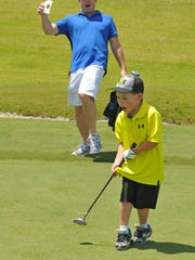 Greyson Steele, 4, is all smiles, as is his dad Chris Steele of Melbourne, after the boy's putt rolled into the cup at a recent golf clinic for children, held at Duran Golf Club in Viera.