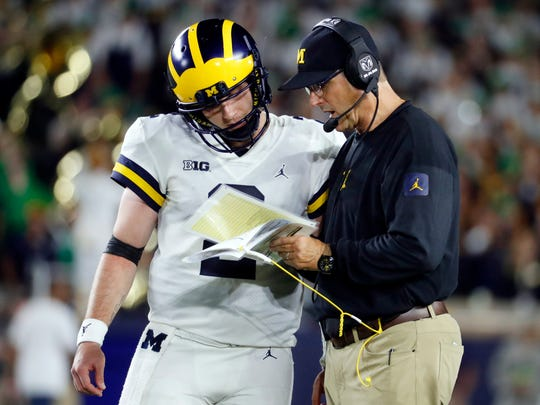 FILE - In this Saturday, Sept. 1, 2018, file photo, Michigan quarterback Shea Patterson (2) talks to head coach Jim Harbaugh during the second half of an NCAA football game against Notre Dame in South Bend, Ind. Traditional Big Ten powers Wisconsin, Michigan and Michigan State have lost out-of-conference games. Slow starts, however, doesn't mean the conference is out of the national title hunt. (AP Photo/Paul Sancya, File)