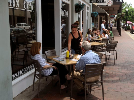 Diners eat at The Tin Cow during Shop Sunday in downtown Pensacola.