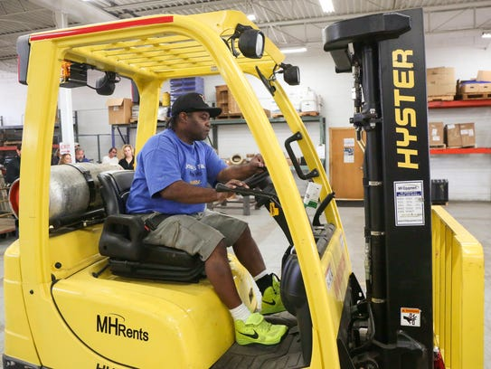 Mcarther Gunn of Des Moines operates a forklift during