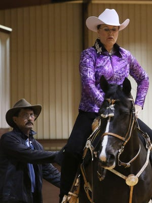 Fred Weaver combs Wicked William's tail as the horse and rider Lisa Weaver wait to enter the ring during a show at the Ike Hamilton Expo Center in West Monroe on Friday.