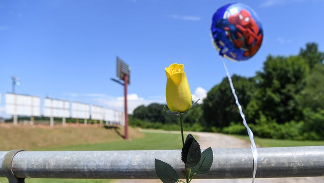 A yellow rose and a balloon are attached to the fence at the Greenville-Pickens Speedway in Easley on Saturday.