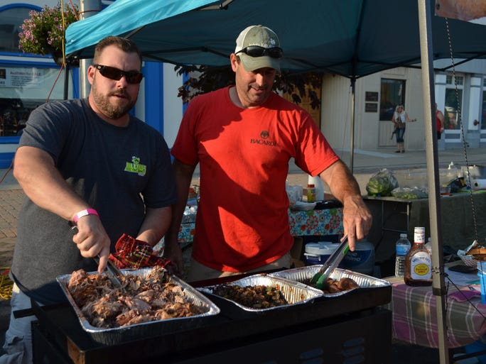 Jason Schoch and Jesse Morvay, owners of J&J BBQ of Vineland, prepare pulled pork and sausage with peppers and onions.