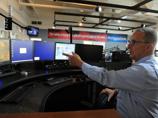 William Harry, director of emergency communications, explains how a dispatch station works at the facility in Salinas.