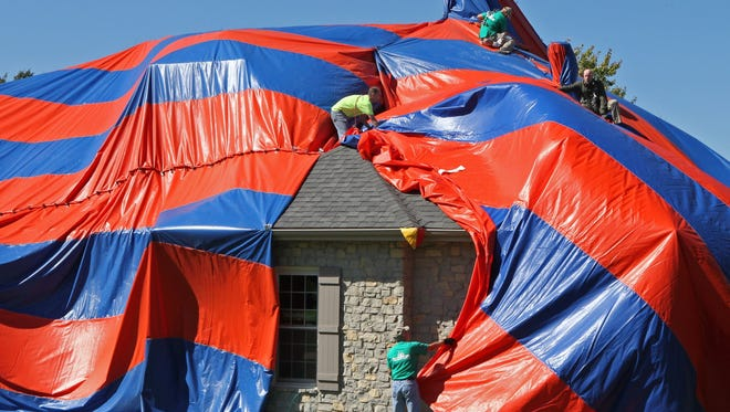 In this photo taken on Sunday, Oct. 5, 2014, workers cover a house with a tarp in preparation for fumigating the home to get rid of brown recluse spiders.