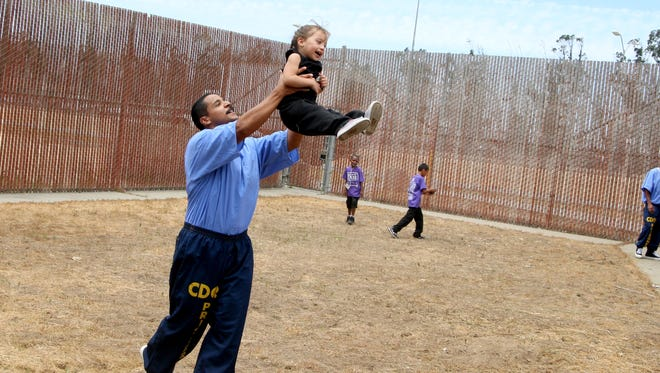 James Ortega spends time with his little girl Mary during an early Father's Day celebration at Salinas Valley State Prison.