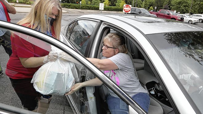 Debbie Bolyard (left) collects donations from Melanie Greer during a school-supply donation drive sponsored by the Reynoldsburg Lions Club and city of Reynoldsburg on Aug. 15 at City Hall, 7232 E. Main St. All donations collected will be used to create supply kits for students in the district. The supplies will be distributed from 10 a.m. to 1 p.m. Saturday, Aug. 29, at City Hall.