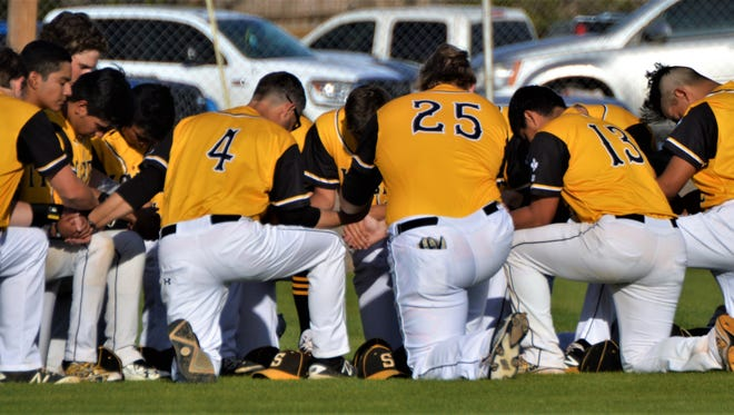Snyder's baseball team joins hands for a pregame prayer before Friday's game with Sweetwater in Snyder.