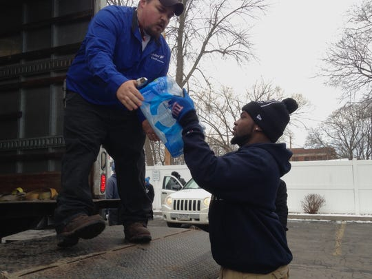 Conrad Gadson of Rochester, right, helps Kevin Mitchell of Cook Moving Systems load a truck with water.