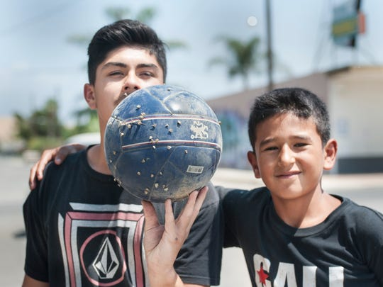 Israel Barba, 15, left, goalie and captain of the Ivanhoe Boys & Girls Club soccer team, shows his soccer ball full of goatheads from the dirt lot across from the club.