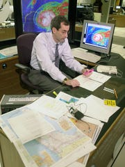 National Hurricane Center spokesman Ed Rappaport studies charts and maps as a hurricane approaches.