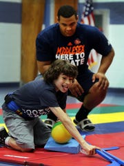 Branden Barnes, a recent Edison High School graduate, interacts with Tanner Mercado from Edison during the Middlesex County All-Stars' visit to the Lakeview School in Edison on Monday.