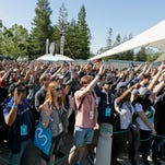 People wave while waiting to take their seats to hear the keynote address of the Google I/O conference in Mountain View, Calif.