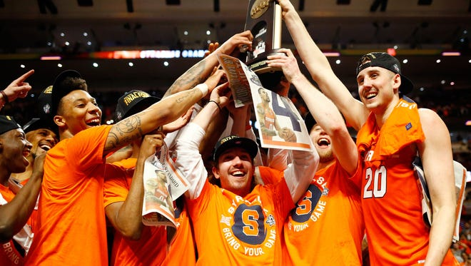 The Syracuse Orange celebrate their 68-62 win over Virginia during the NCAA tournament Midwest Regional Final at United Center on Sunday.