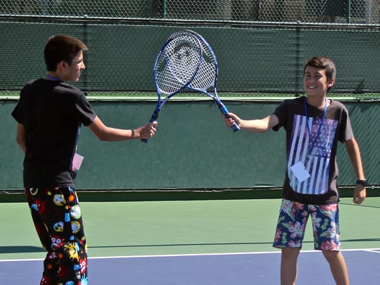Two young tennis players celebrate a point Thursday at the Indian Wells Tennis Garden. About 50 East Valley kids had the opportunity to improve their tennis skills by learning from two tennis legends: Rosie Casals and Tory Fretz.