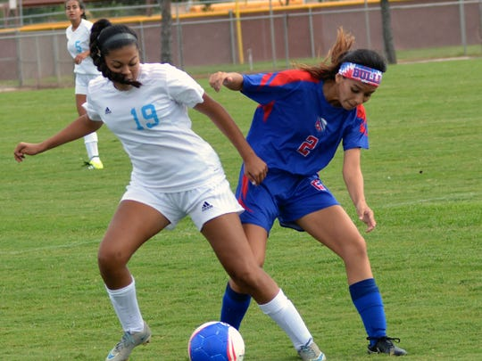Las Cruces High's Sonrisa Salazar (right) for the Bulldawgs fights for a lose ball against Cleveland High's Brianna Gros (left) Saturday morning at High Noon Soccer Complex.
