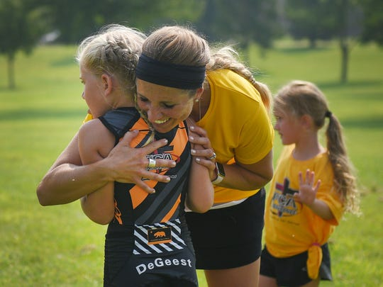 Alicia DeGeest gives her daughter Evelyn DeGeest a hug after she finishes the Parks and Recreation Youth Triathlon at Kuehn Park Friday, Aug 10, in Sioux Falls.