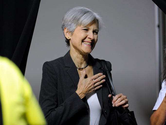 Dr. Jill Stein, center, waits to talk to the media