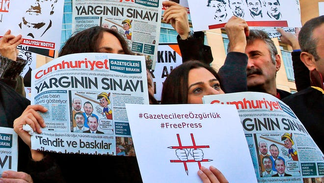 In this file photo dated Oct. 31, 2017, demonstrators hold placards and copies of the Cumhuriyet daily newspaper as they stage a protest outside a court where the trial of about a dozen employees of the newspaper on charges of aiding terror groups, was held.