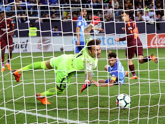 Barcelona's Coutinho scores his side's 2nd goal during a Spanish La Liga soccer match between Malaga and Barcelona in Malaga, Spain, Saturday, March 10, 2018. (AP Photo/M.Pozo)